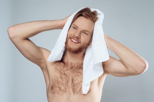 Jovem homem barbudo está limpando o cabelo molhado por toalha
