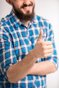 Jovem homem barbudo está mostrando o polegar para cima e sorrindo.