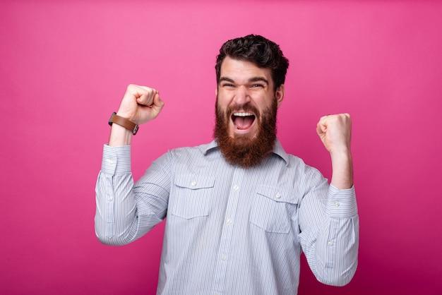 Jovem homem barbudo, fazendo o vencedor gesticular em fundo rosa.