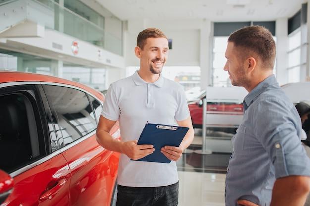 Jovem homem barbudo fica na frente do cliente e sorri. ele segura um tablet de plástico com as duas mãos. as pessoas estão na frente do carro vermelho e bonito. o cliente está falando sério.