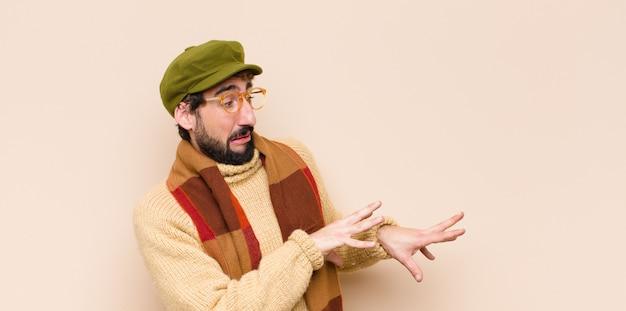 Jovem homem barbudo frio se sentindo enojado e com náuseas, se afastando de algo desagradável, fedorento ou fedorento, dizendo eca