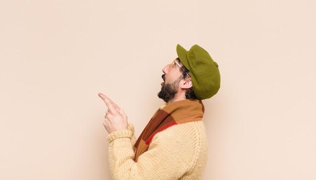 Jovem homem barbudo frio sentindo-se maravilhado e com a boca aberta apontando para cima com um olhar chocado e surpreso