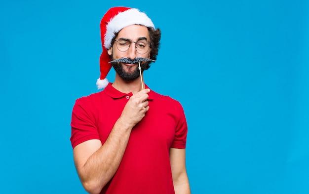Jovem homem barbudo louco com chapéu de papai noel. conceito de natal