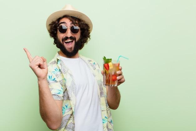 Jovem homem barbudo louco com um cocktail. conceito de turista
