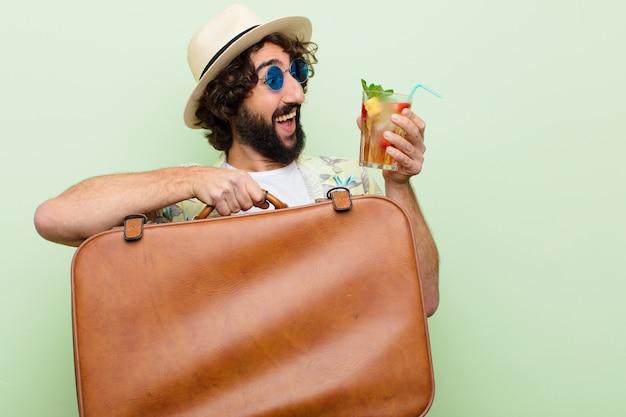 Jovem homem barbudo louco com um cocktail. conceito de viagens