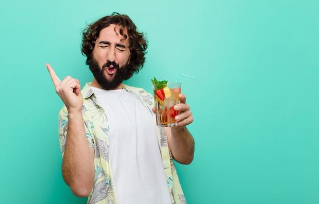Jovem homem barbudo louco com um cocktail. turista