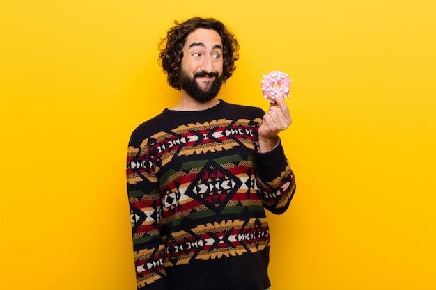 Jovem homem barbudo louco com um donut de açúcar