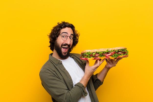 Jovem homem barbudo louco com um sanduíche gigante.