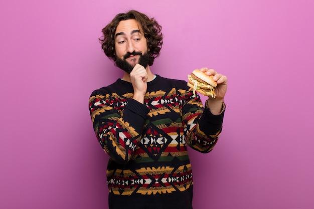 Jovem homem barbudo louco comendo um hambúrguer