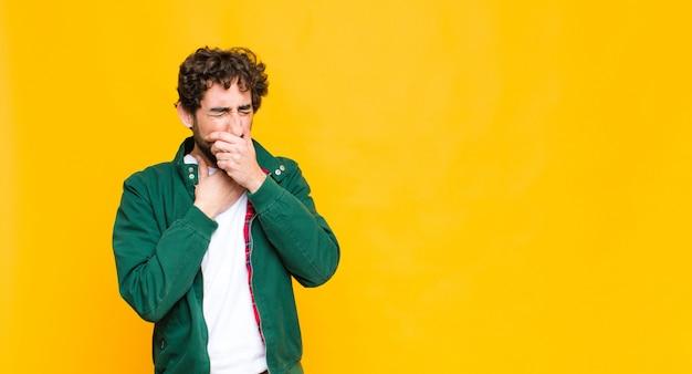 Jovem homem barbudo louco se sentindo doente com dor de garganta e sintomas de gripe, tossindo com a boca coberta por parede