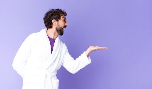 Jovem homem barbudo louco vestindo roupão contra a parede