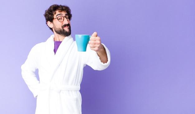 Jovem homem barbudo louco vestindo roupão e tomando um café