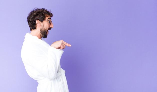 Jovem homem barbudo louco vestindo roupão na parede do espaço de cópia
