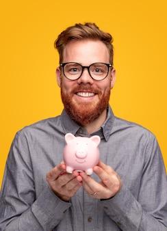 Jovem homem barbudo otimista com camisa casual e óculos, demonstrando o cofrinho rosa para economizar dinheiro contra o fundo amarelo
