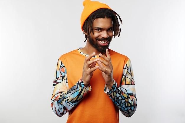 Jovem homem barbudo, pele escura e chapéu laranja isolado
