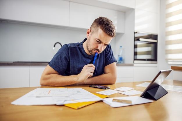 Jovem homem barbudo sério sentado à mesa de jantar e calculando as despesas mensais. há muitas contas a pagar.