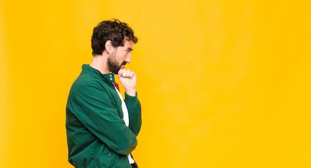 Jovem homem barbudo sobre o espaço da cópia de parede laranja.
