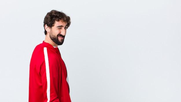 Jovem homem barbudo vista traseira feliz e amigável, sorrindo e piscando um olho para você com uma atitude positiva sobre a parede do espaço de cópia