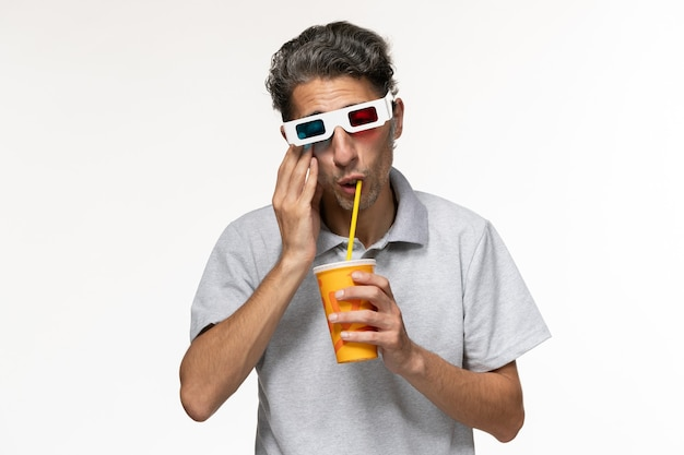 Jovem homem bebendo refrigerante de frente e usando óculos escuros na superfície branca