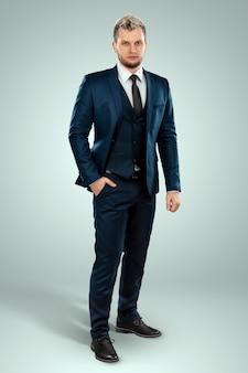 Jovem homem bem-vestido em um terno de negócios em um fundo claro