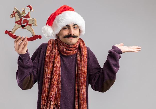 Jovem homem bigodudo usando chapéu de papai noel de natal com um lenço quente em volta do pescoço segurando um brinquedo de natal confuso, sorrindo, apresentando-se com o braço da mão em pé sobre a parede branca
