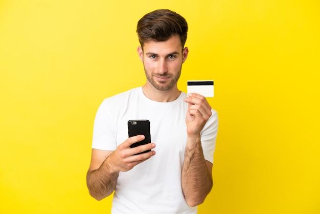 Jovem homem bonito, caucasiano, isolado em um fundo amarelo, comprando com o celular com um cartão de crédito
