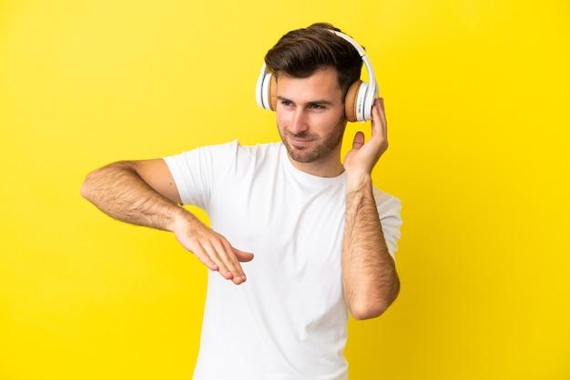 Jovem homem bonito, caucasiano, isolado em um fundo amarelo, ouvindo música e dançando