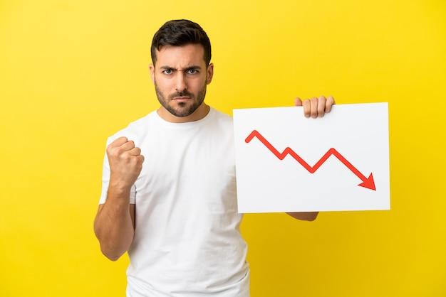 Jovem homem bonito, caucasiano, isolado em um fundo amarelo, segurando uma placa com um símbolo de seta decrescente de estatísticas e com raiva
