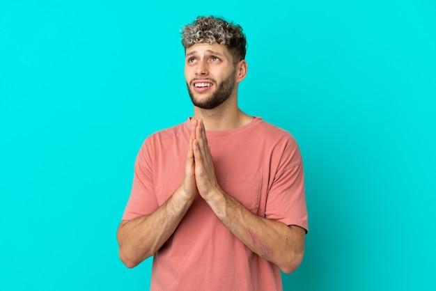 Jovem homem bonito caucasiano isolado em um fundo azul mantém as palmas das mãos juntas. pessoa pede algo
