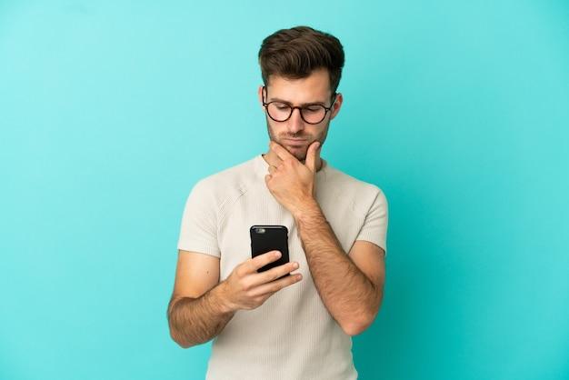 Jovem homem bonito, caucasiano, isolado em um fundo azul, pensando e enviando uma mensagem