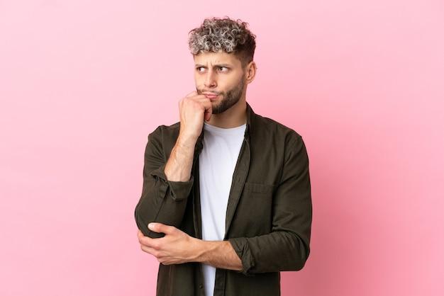 Jovem homem bonito, caucasiano, isolado em um fundo rosa, tendo dúvidas e pensando