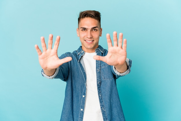 Jovem homem bonito caucasiano isolado mostrando o número dez com as mãos.