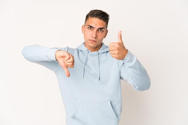 Jovem homem bonito caucasiano isolado mostrando os polegares para cima e para baixo, difícil escolher o conceito