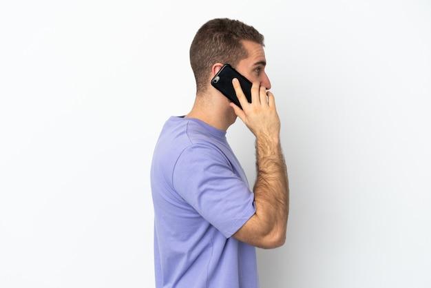 Jovem homem bonito, caucasiano, isolado na parede branca, conversando com alguém ao telefone celular