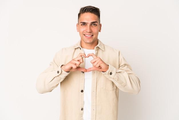 Jovem homem bonito caucasiano isolado sorrindo e mostrando uma forma de coração com as mãos.