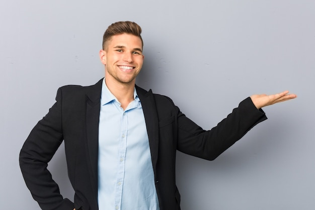 Jovem homem bonito caucasiano mostrando um espaço de cópia na palma da mão e segurando a outra mão na cintura.