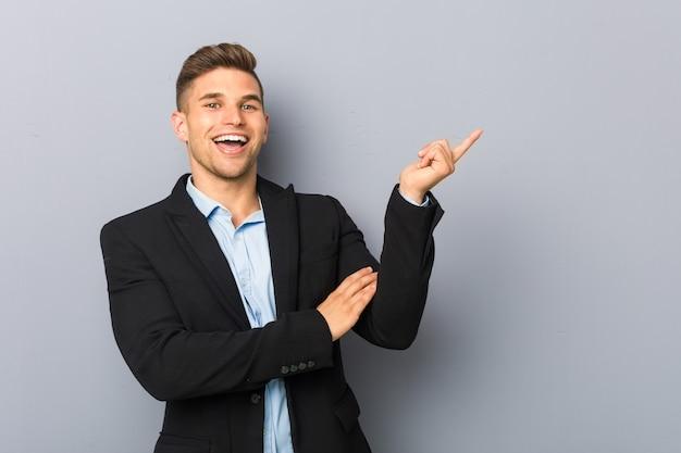 Jovem homem bonito caucasiano sorrindo alegremente, apontando com o dedo indicador para longe.