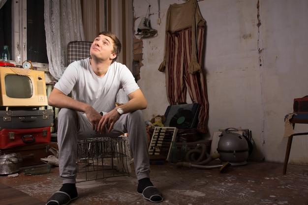 Jovem homem bonito com camisa casual sentado na gaiola na sala de lixo bagunçado, olhando para cima