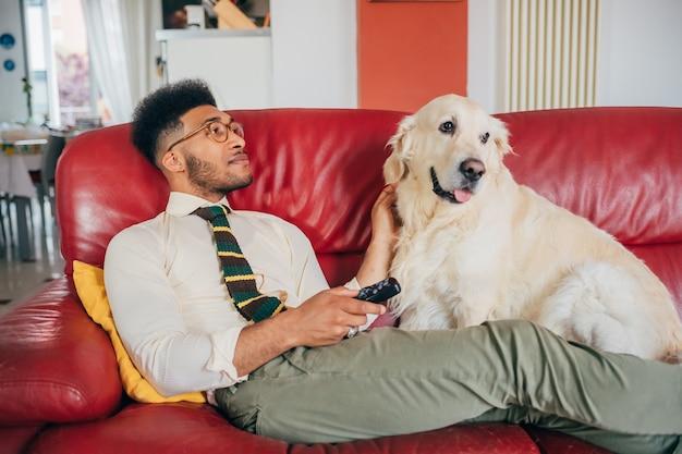 Jovem homem bonito interior em casa relaxando com seu cão surfando canal usando o controle remoto