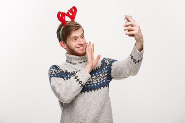 Jovem, homem bonito, usando um selfie ou falando no rosto