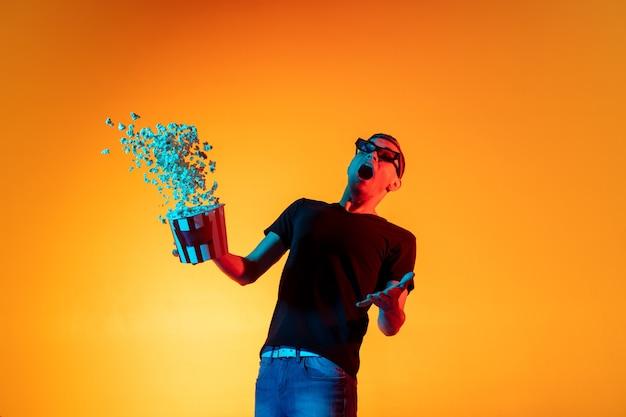 Jovem homem branco com microfone isolado sobre fundo laranja de estúdio em luz de néon