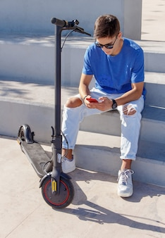 Jovem homem branco com smartphone sentado ao ar livre perto de scooter elétrico e usando smartphone