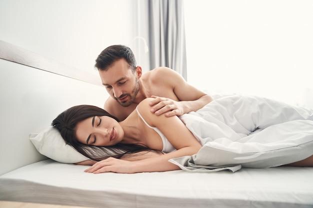 Jovem homem branco com um corte de cabelo curto, curvado sobre uma linda mulher dormindo na cama