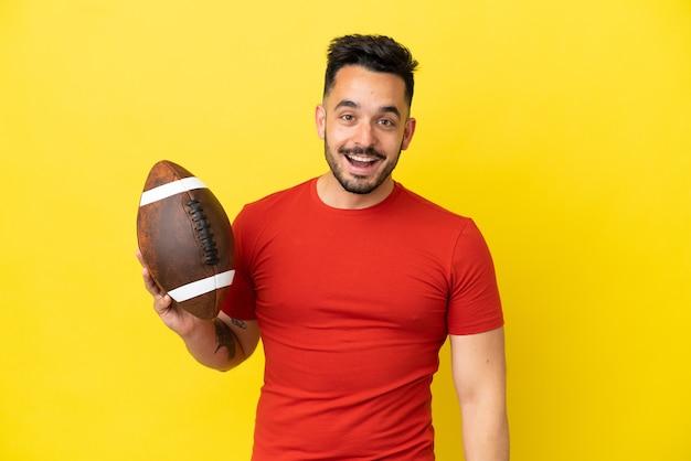 Jovem homem branco jogando rúgbi isolado em um fundo amarelo com expressão facial surpresa