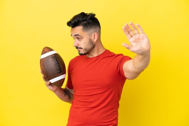 Jovem homem branco jogando rugby isolado em um fundo amarelo, fazendo gesto de pare e desapontado