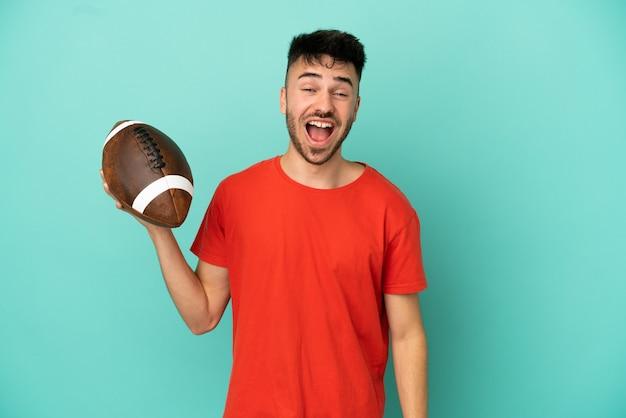 Jovem homem branco jogando rugby isolado em um fundo azul com expressão facial surpresa