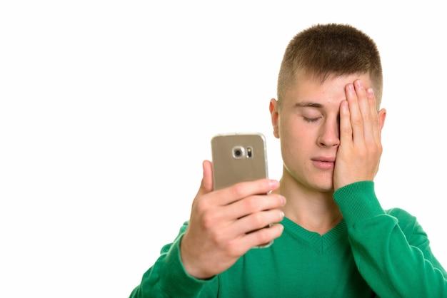 Jovem homem branco segurando um celular e parecendo cansado de olhos fechados