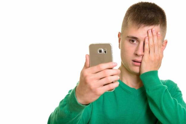 Jovem homem branco segurando um celular e parecendo estressado