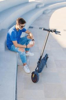 Jovem homem branco sentado ao ar livre perto de uma scooter elétrica e bebendo café para viagem