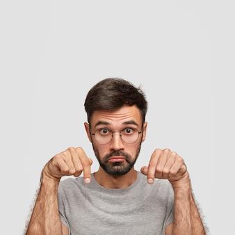 Jovem homem branco tem expressão de surpresa, aponta para baixo com os dois dedos indicadores, franze os lábios em perplexidade, demonstra algo, isolado sobre a parede branca com espaço de cópia para cima